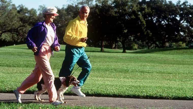 Pareja de ancianos corriendo en el parque con perro
