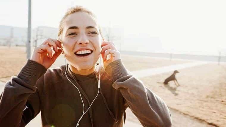 Joven escuchando música con un perro de fondo