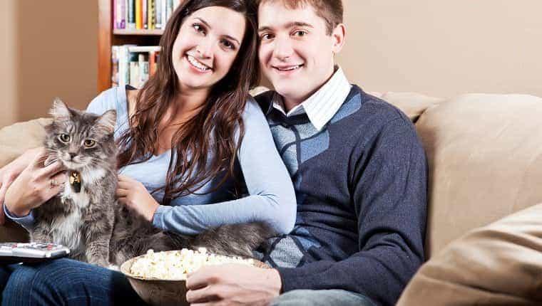 Una pareja sentada en el sofá relajándose en casa