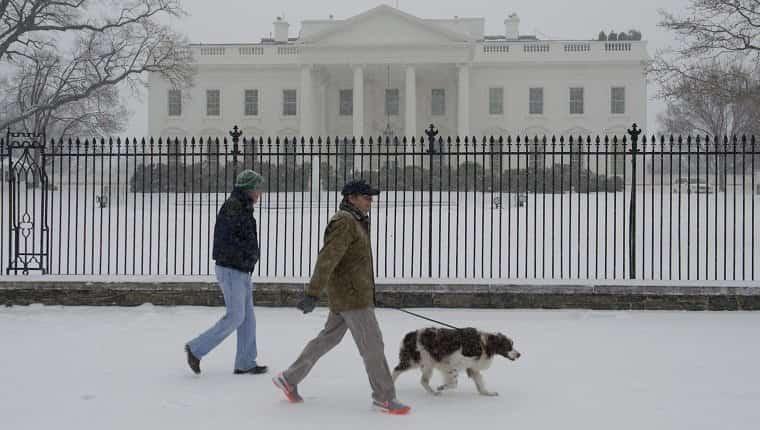 La gente paseaba a un perro durante una tormenta de nieve frente a la Casa Blanca en Washington, DC, el 3 de marzo de 2014. La nieve comenzó a caer en la capital del país el lunes, y las autoridades advirtieron a la gente que se mantuviera alejada de las carreteras heladas y traicioneras, un escenario que se ha vuelto familiar para los residentes del Medio Oeste, Este e incluso el Sur Profundo este año.  Las escuelas fueron canceladas, el servicio de autobús se interrumpió en algunos lugares y se ordenó a los funcionarios del gobierno federal en el área de DC que se quedaran en casa el lunes.