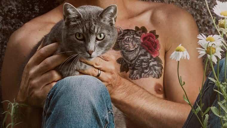 Hombre con tatuaje de gato y su gato mascota