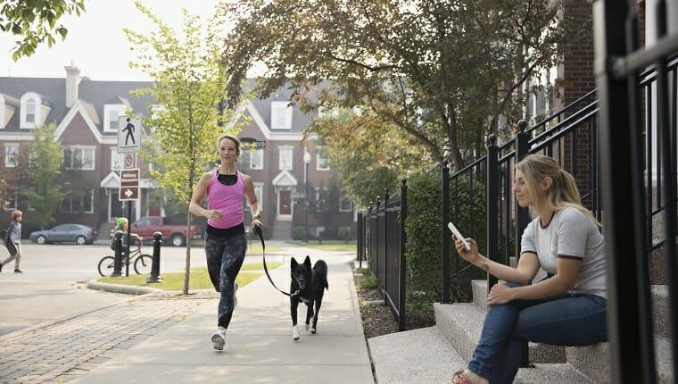 Corredoras corriendo con un perro y una mujer enviando mensajes de texto con su teléfono celular en la acera del barrio