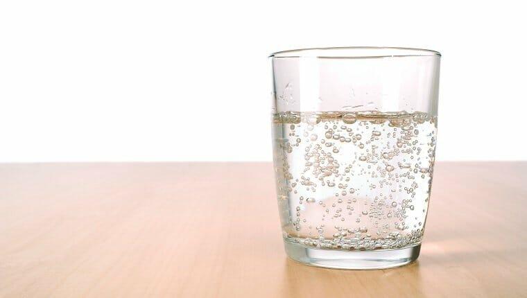 Vaso de agua con gas sobre la mesa